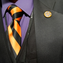 Close up of suit and orange and black striped tie
