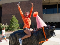 Student celebrates on top of Bengal statue in Union Quad.